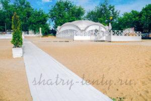 арочный шатер для свадьбы с деревянными дорожками на песке