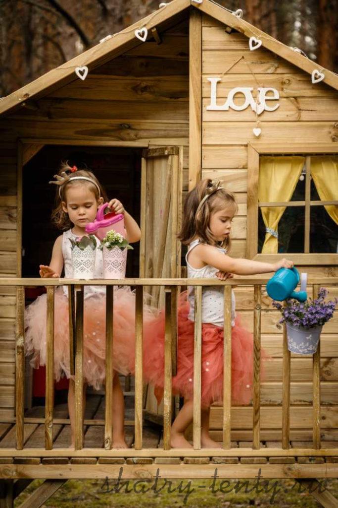 девочки играют в детском домике из деревянного бруса