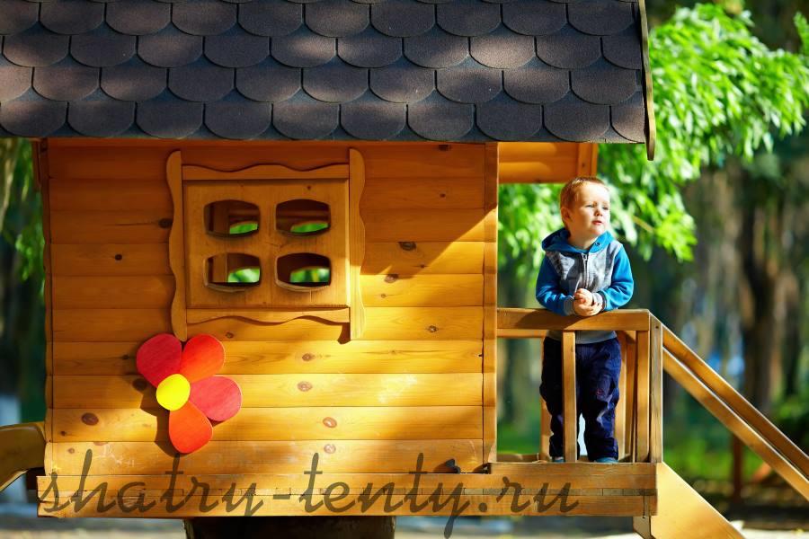 мальчик на крыльце детского домика из натурального дерева