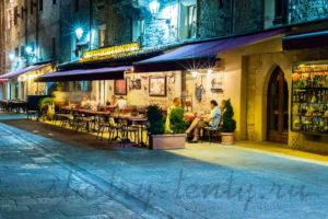 освещение уличного пристенного кафе под маркизами