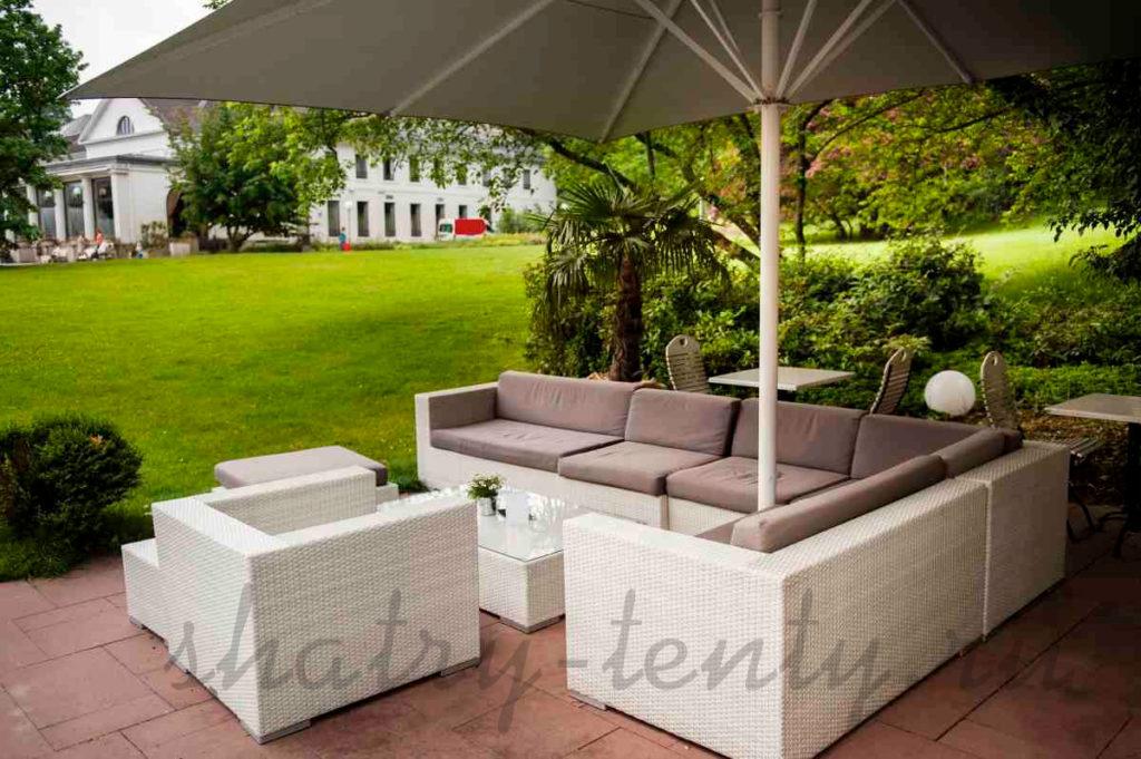 ротанговый диван и кресло под зонтом в кафе