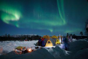 Северное сияние над зимними большими туристическими шатрами Maverick Cosmos