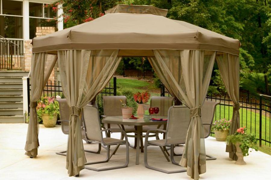 Красивый садовый шестигранный шатер возле дома