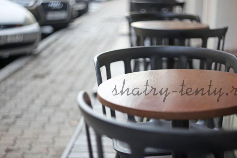 Деревянные черные стулья и столы в кафе на улице