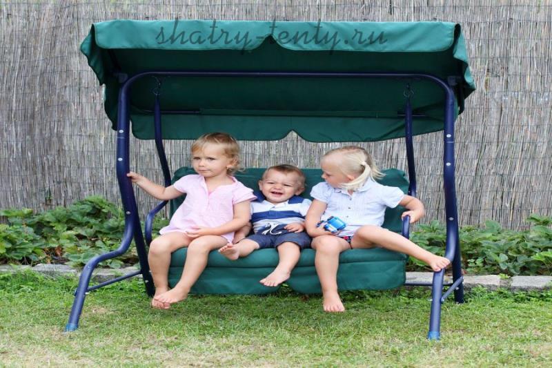 Трое деток на детских переносных качелях на дачном дворе