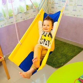 Мальчик в детском подвесном гамаке качели