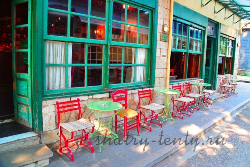Красные деревянные и металлические уличные стулья и зелёные столы