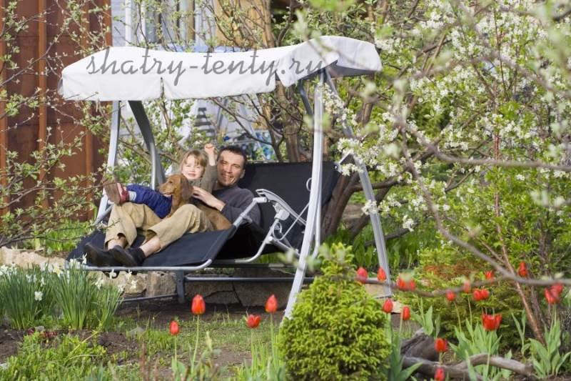 Папа с дочкой на металлических садовых качелях на загородном участке