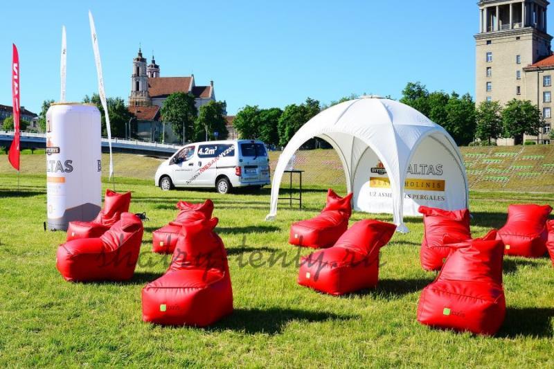 Красные мягкие переносные уличные кресла на газоне