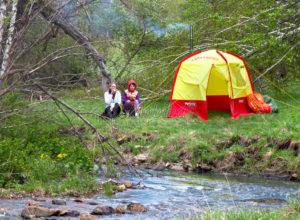 Красно-желтая ранцевая мобильная баня «Кайфандра» рядом с небольшой речкой