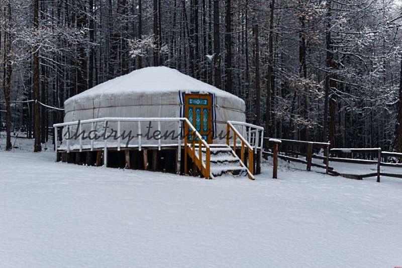 Разборная юрта под снегом, установленная на склоне и выровненная с помощью деревянного основания