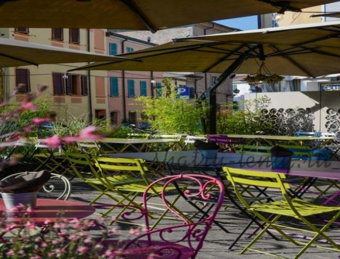 Уличные разноцветные складные стулья и столы под зонтиками