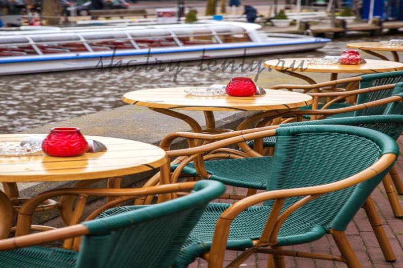 Бирюзовые стулья из пластикового ротанга на деревянной основе, и деревянные столы