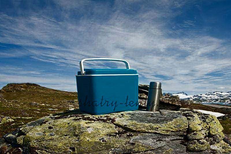 Пластиковый изотермический контейнер и термос в гористой местности