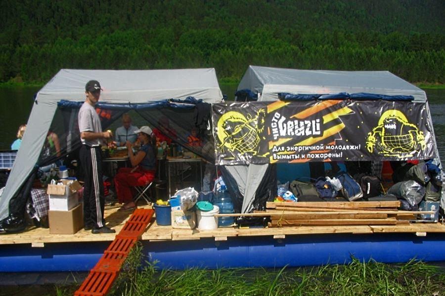 Плот для сплава по реке из сборной платформы закрепленной на раму и с двумя шатрами с москитной сеткой
