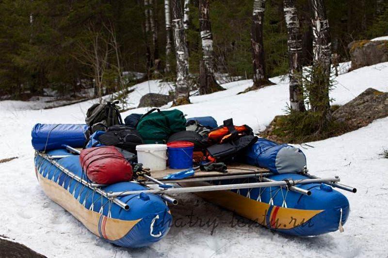 Синий моторно-гребной плот-катамаран подготовленный к сплаву по реке